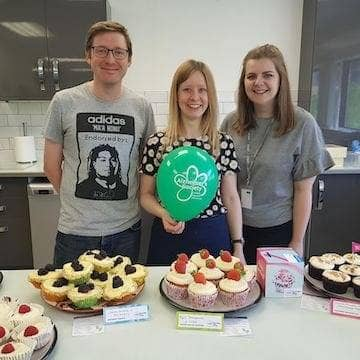 staff posing with their cupcakes at a charity bake sale