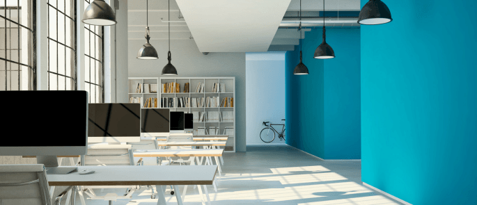 an office space with five desks and a bookcase