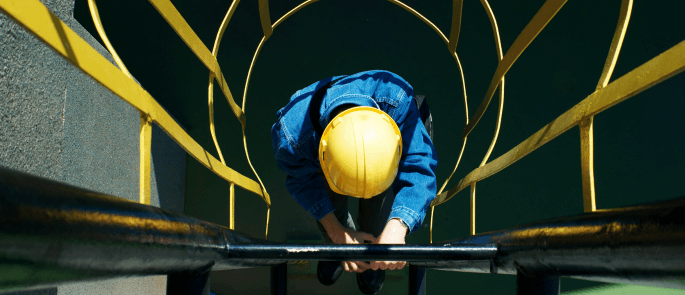 Worker climbing a ladder into an excavation site