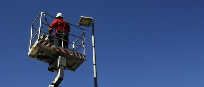 Worker working at height on a cherry picker to fix light