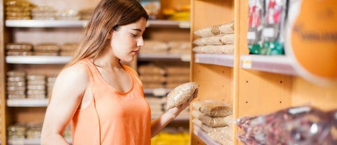 woman in a shop looking at a food product and the food allergen labels on it