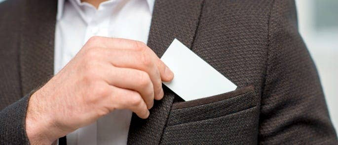 A man putting a business card in his jacket pocket