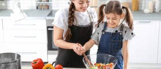 Childminder making salad with young girl