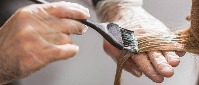 A hairdressing using gloves to reduce occupational hazards such as contact dermatitis