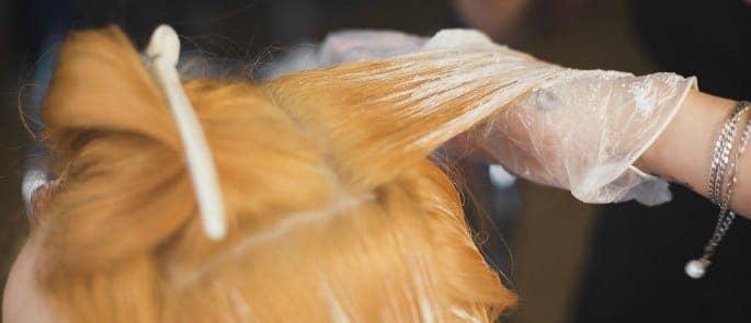 A hairdresser bleaching hair wearing gloves to protect against bleach