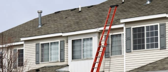 A ladder extended to a house roof