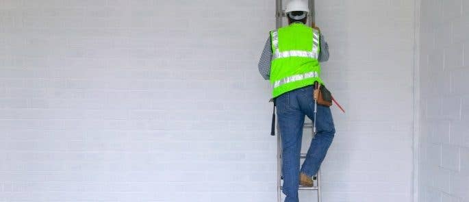 Man in protective clothing climbing a ladder