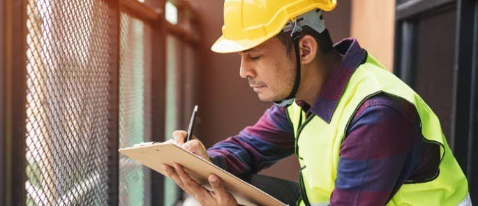 Man in protective clothing at a building site taking notes
