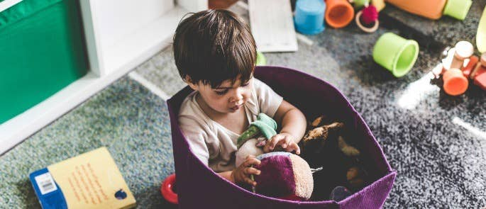 Toddler playing with toys in basket