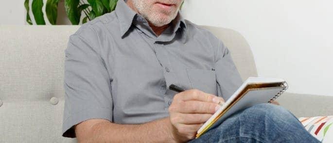 man writing a mood log
