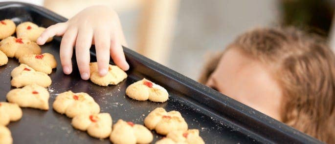 Child taking cookie off a baking tray