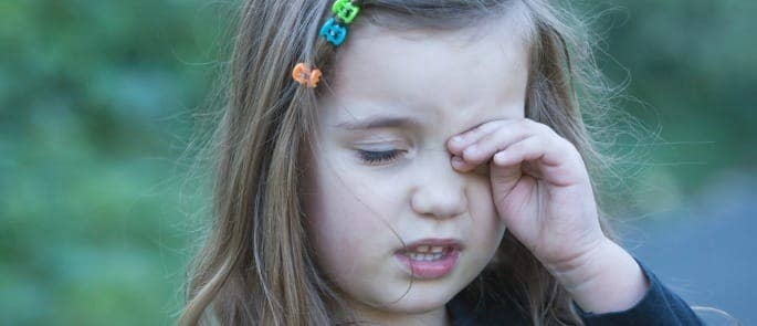 child looking unhappy with hand to her face