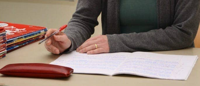 female writing in a notepad on a teachers' desk