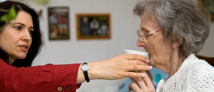 A carer assisting a dementia patient with drinking water