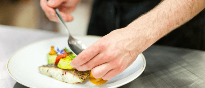 A chef plating up a dish with clean hands