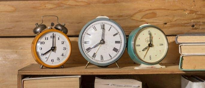 Three clocks on a shelf
