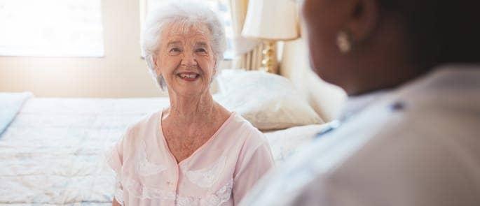 carer and elderly woman care home bedroom