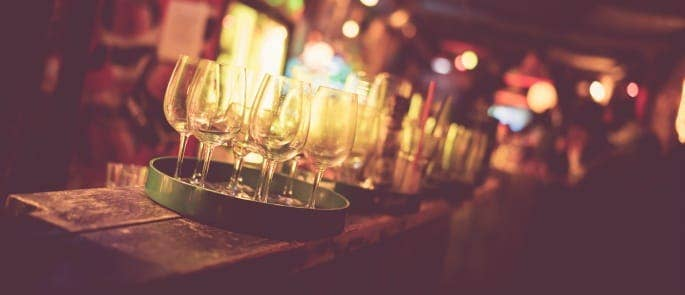 A busy bar with wine glasses on a tray