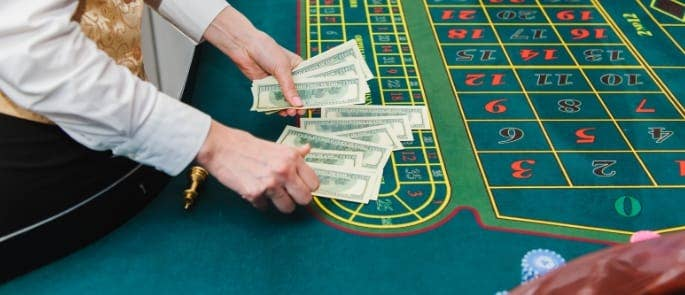 gambler placing money on roulette casino table