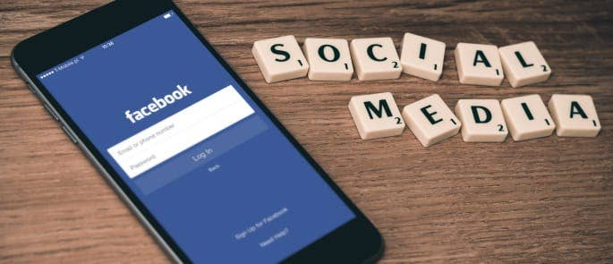 Facebook on an iPhone next to scrabble letters spelling 'social media'
