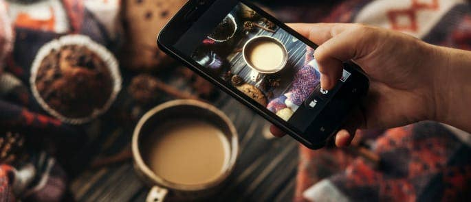A teenage lifestyle blogger taking an artsy photo of coffee for Instagram