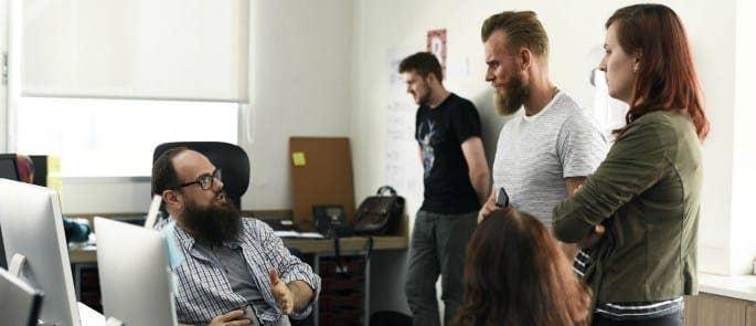 A team talking around a computer