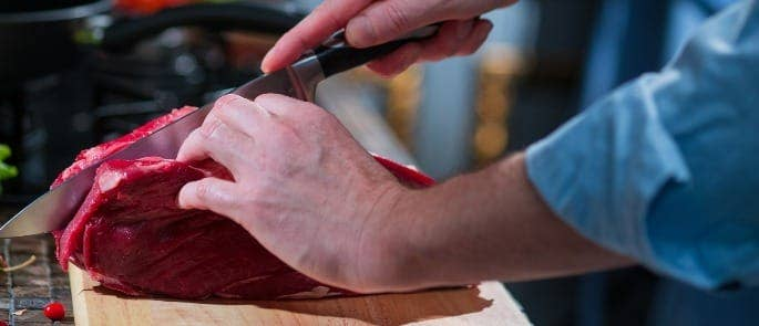 Chef slicing raw cut of beef