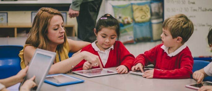 A teaching assistant helping pupils correct their work on a tablet using marking symbols