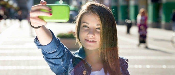 Teenager using Snapchat on her mobile phone to send a selfie