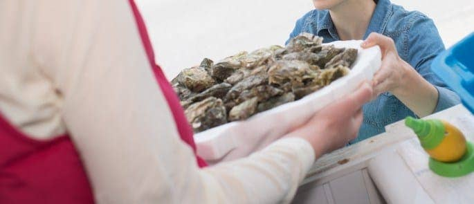 Waitress passing shellfish to diner