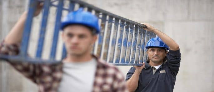Two men carrying a ladder safely