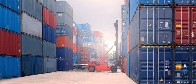 red cargo lorry surrounded by shipping containers