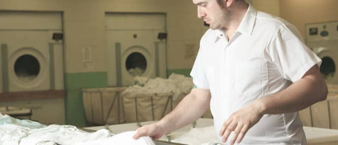 man working inside a care home laundry room