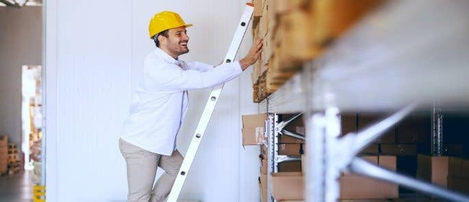 Man climbing a ladder in a stockroom