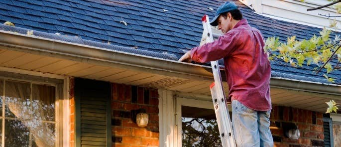 Man standing on a ladder to look at house gutters
