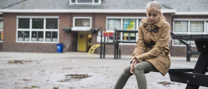 Teenage girl sat in the school playground