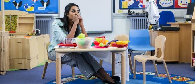 Worried female teacher sat in classroom