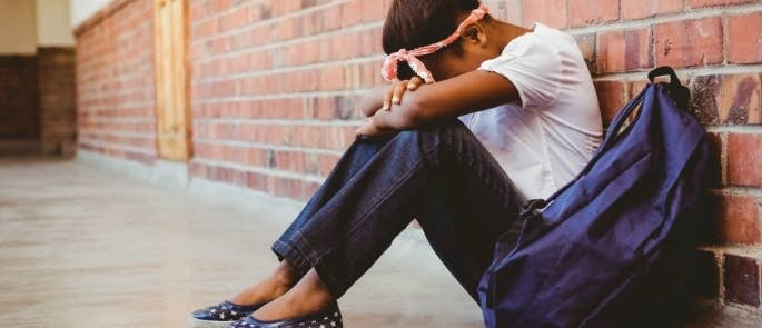 Distressed teenager sitting against a wall