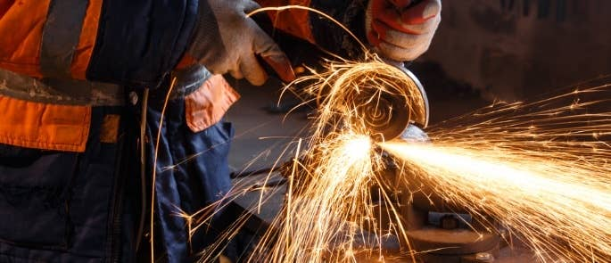 Worker cutting metal with an angle grinder