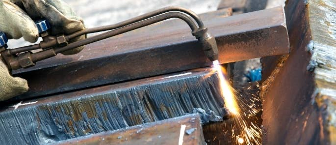 Worker using blow torch to cut metal sheet