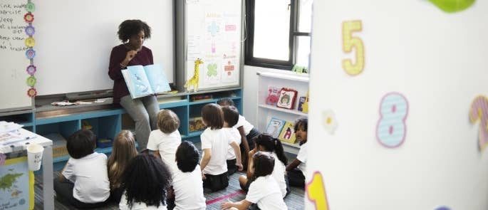 Primary school teacher reading a book to children