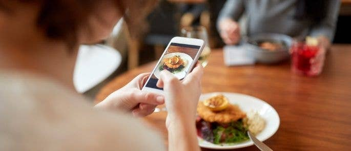 Lady using mobile phone to take picture of her food.
