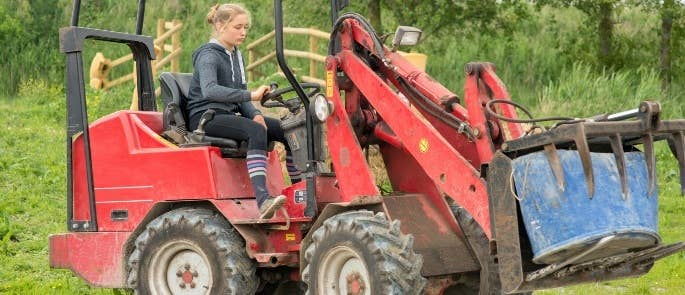 Farmer using lifting equipment on her farm