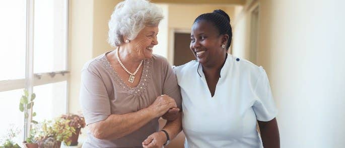 Caregiver and patient walking through care home