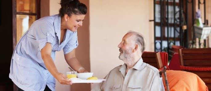 Carer serving gentleman meals in his home