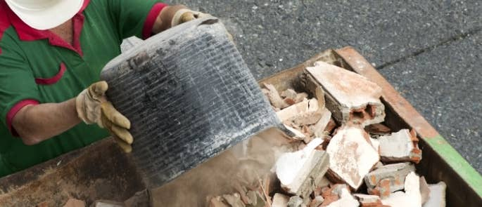 Worker putting brick waste into a construction skip
