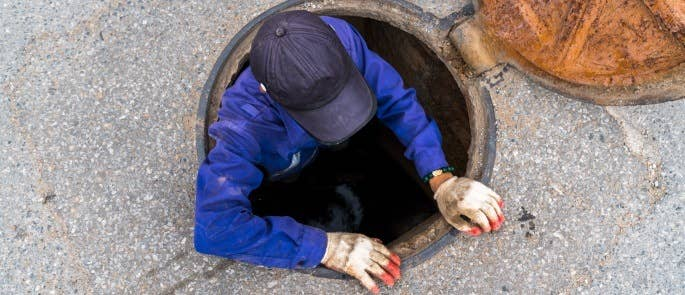 Lone worker entering a manhole