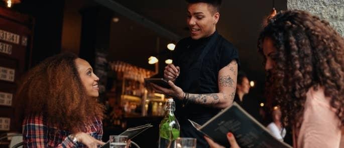 Customers reading menus and ordering at a restaurant