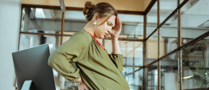 Pregnant lady stands at office window looking warm