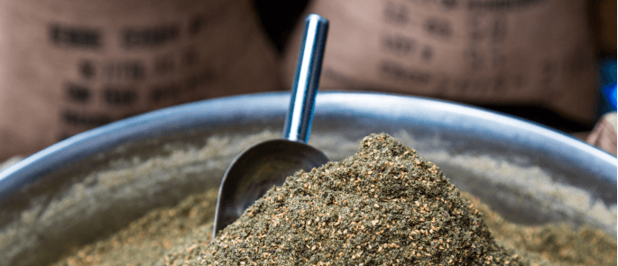 close up of spice blend in an open container with a scoop in the top.